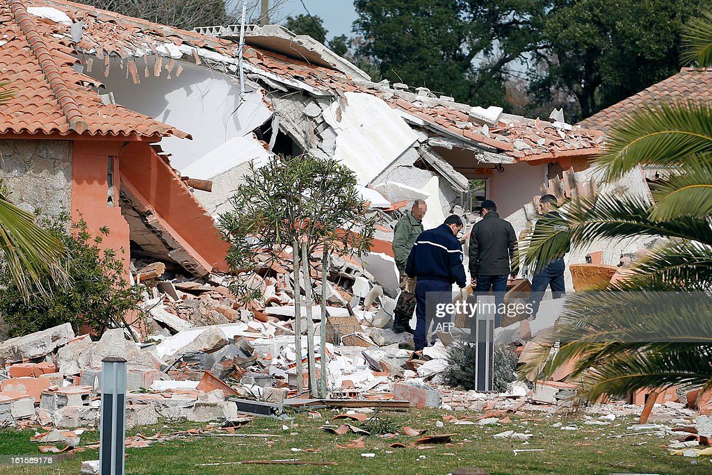 French Gendarmes investigate in the rubble of a house destroyed by a blast, injuring a man and a child, on February 12, 2013, in Porto-Vecchio, in the French Mediterranean island of Corsica. The reasons of the blast are still unknown.