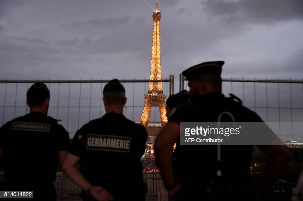 French gendarmes look towards the Eiffel Tower in Paris on July 13 as US President Donald Trump and French President Emmanuel Macron attend a dinner...