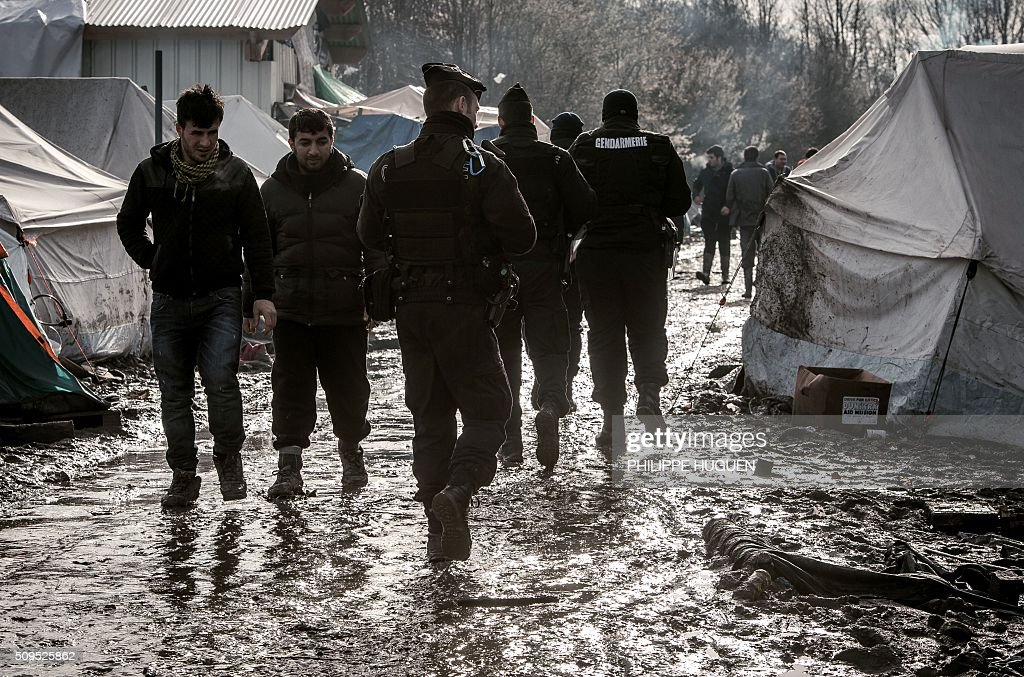 French gendarmes patrol in the so-called 'Jungle' migrant camp in Gande-Synthe where 2,500 refugees from Kurdistan, Iraq and Syria live on February 11, 2016 in Grande-Synthe near the city of Dunkirk, northern France. / AFP / PHILIPPE HUGUEN