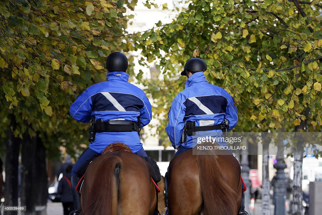 French gendarmes patrol on horses on November 19, 2013 in Paris as a manhunt is under way in the capital for a lone gunman who shot and critically wounded a newspaper photographer in his office on November 18 before opening fire outside a bank headquarters and hijacking a car. Officers on foot and in squad cars fanned across the nervous city, taking up positions outside media offices, along the Champs-Elysees avenue and at entrances to underground train stations. Investigators have so far been unable to identify the gunman, described by French Interior Minister Manuel Valls as 'a real danger'.