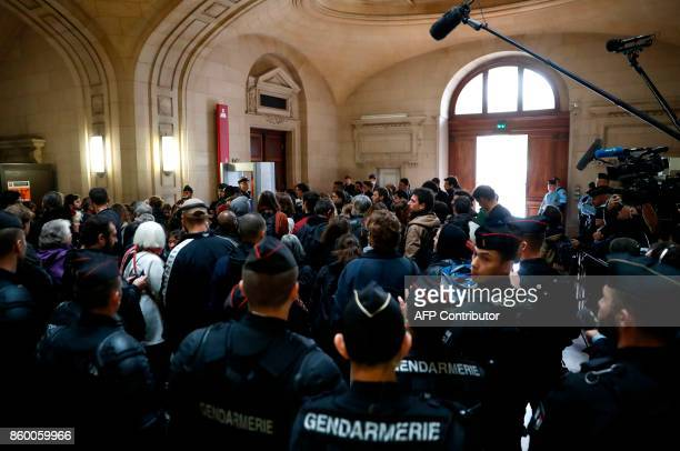 French Gendarmes people and media gather at the entrance of the Paris' courthouse on October 11 during the trial of seven accused over the case of a...