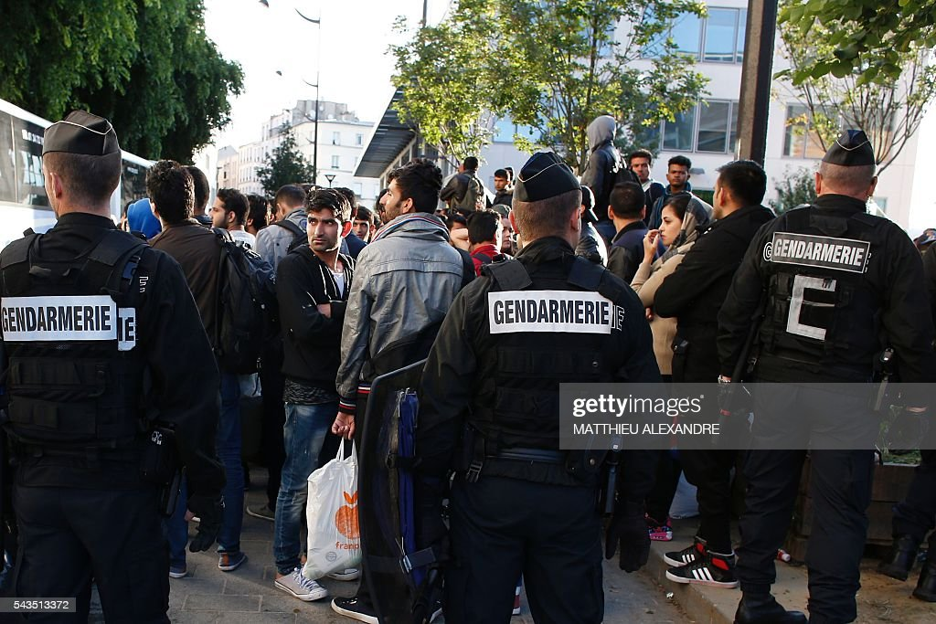 French Gendarmes proceed to the evacuation of migrants at the Pajol hall on June 29, 2016 in Paris. The police started early on June 29, 2016, the evacuation of several hundreds of migrants, from a camp at the former SNCF Hall 'Pajol'. / AFP / MATTHIEU