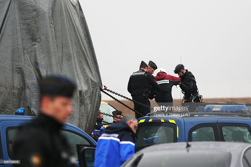 French gendarmes remove Greenpeace's activists from a trailer of a special convoy transporting a lid that is to be installed on the vessel of the nuclear reactor EPR, currently under construction at Flamanville, in Evrecy, northernwestern France, on February 12, 2016. The convoy transporting the lid of 110 tons that measures 5,5 meters in diameter left the Areva plant on Chalon-sur-Saône, eastern France, on the morning of February 8 and is expected to arrive at its destination on February 12. / AFP / CHARLY TRIBALLEAU