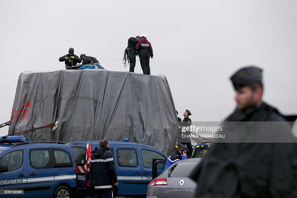 French gendarmes remove Greenpeace's activists from the top of a trailer of a special convoy transporting a lid that is to be installed on the vessel of the nuclear reactor EPR, currently under construction at Flamanville, in Evrecy, northernwestern France, on February 12, 2016. The convoy transporting the lid of 110 tons that measures 5,5 meters in diameter left the Areva plant on Chalon-sur-Saône, eastern France, on the morning of February 8 and is expected to arrive at its destination on February 12. / AFP / CHARLY TRIBALLEAU