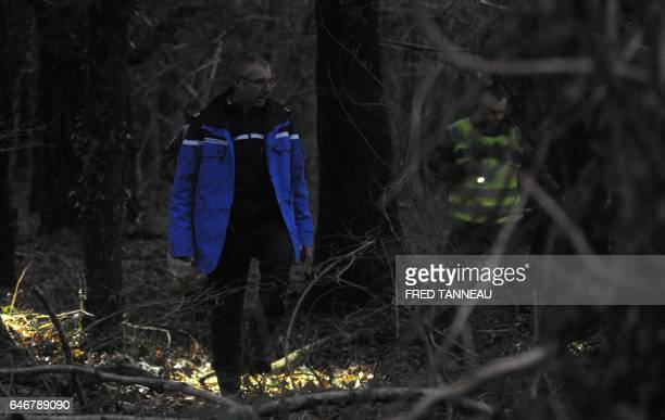French gendarmes search near the site where a healthcare card in the name of a missing person was discovered by a runner on March 1 in Dirinon some...