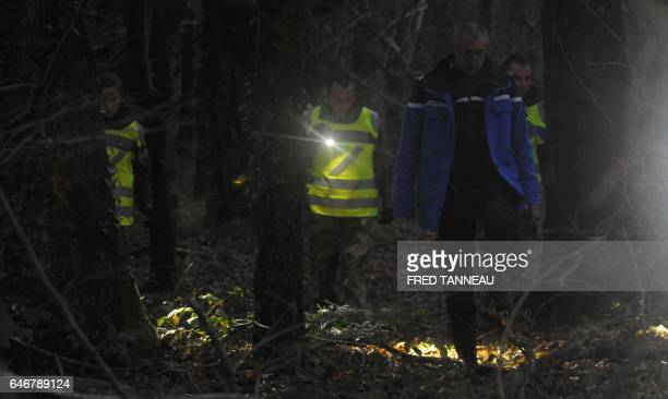 French gendarmes search with flashlights near the site where a healthcare card in the name of a missing person was discovered by a runner on March 1...