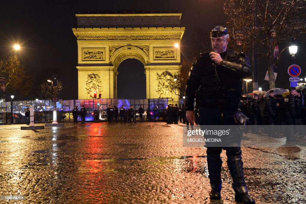 French gendarmes secure the Arch of Triumph area prior to the celebrations for the New Year on the Champs-Elysees avenue in Paris, late on December 31, 2012. AFP PHOTO / MIGUEL MEDINA