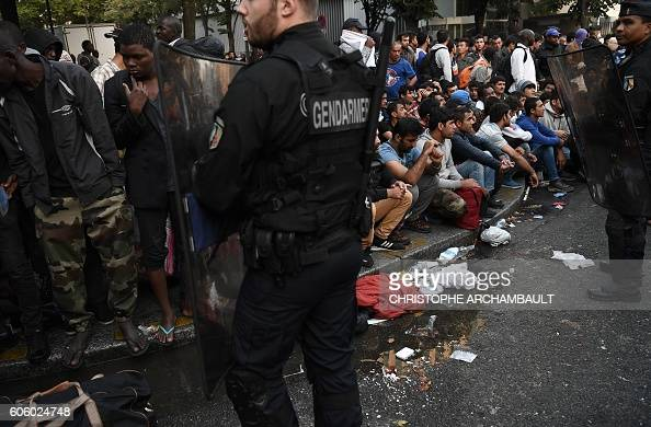 TOPSHOT French gendarmes secure the area as migrants wait and gather before being evacuated from a makeshift migrant camp set up between the metro...