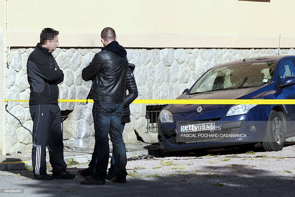 French gendarmes speak next to the place where the Ajaccio's gendarmerie was hit by rockets two days before, on December 7, 2013 in the French Mediterranean island of Corsica.