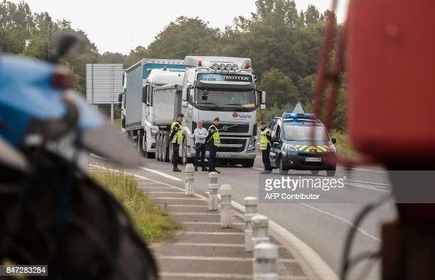 French Gendarmes stand by a truck driver as some 60 duck farmers block roads beetween Dax and MontdeMarsan in Tartas on September 15 2017 as part of...