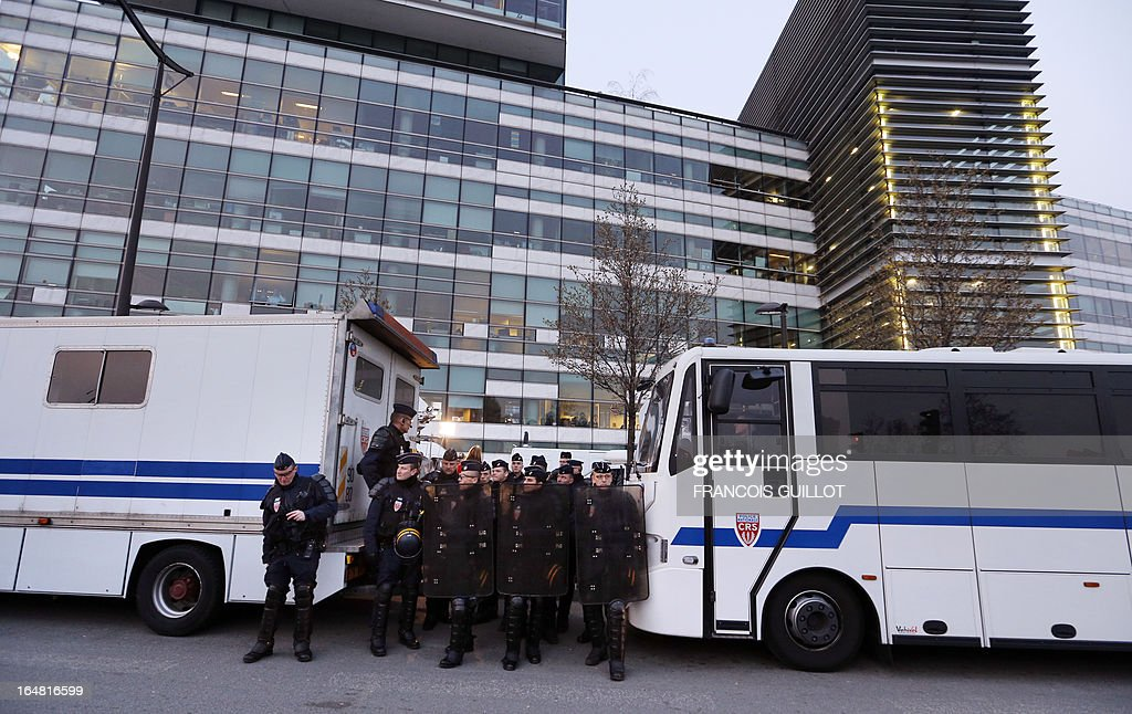 French gendarmes stand by during a protest by members of the movement 'La Manif Pour Tous', who are opposed to same-sex marriage, on March 28, 2013, outside the headquarters of France Television group in Paris, while the French president is interviewed during the broadcast news on the TV channel France 2. AFP PHOTO / FRANCOIS GUILLOT