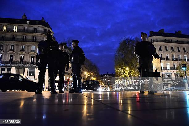 French gendarmes stand guard at Place de la Republique in Paris on November 22 2015 as people gather to pay tribute for the victims of the November...