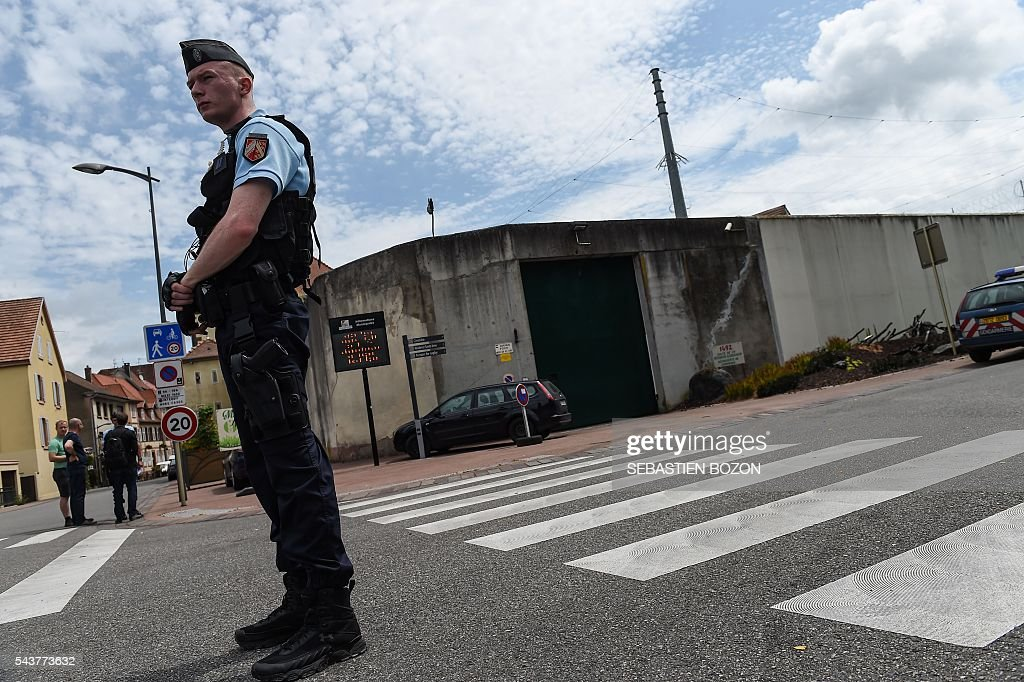 French gendarmes stand guard at the entrance of the Ensisheim prison, northeastern France, where a psychologist is taken hostage by a prisoner on June 30, 2016. / AFP / SEBASTIEN