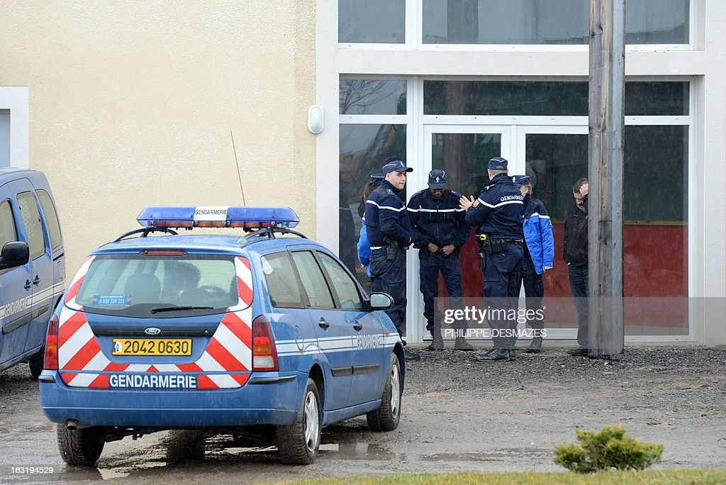 French gendarmes stand guard in front of a construction firm offices in the central France city of Chalain d'Uzore on March 6, 2013, where a man committed suicide after killing his wife and her lover, the construction firm manager. The deceived husband, aged fifty years, shot his rival in the knee before leaving. While the company manager called the fire department, the attacker went back and shot the two lovers. When firefighters arrived on the scene, the gunman stabbed himself twice in the stomach and the heart, firefighters were unable to revive him. AFP PHOTO / PHILIPPE DESMAZES