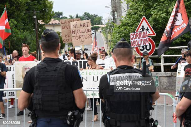 French gendarmes stand guard in front of protesters during a demonstration against bullfighting on June 24 2017 in the French city of La Brede...