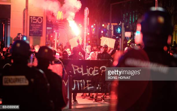 TOPSHOT French gendarmes stand guard in front of protesters holding a flare and a banner during a demonstration against police brutality on February...