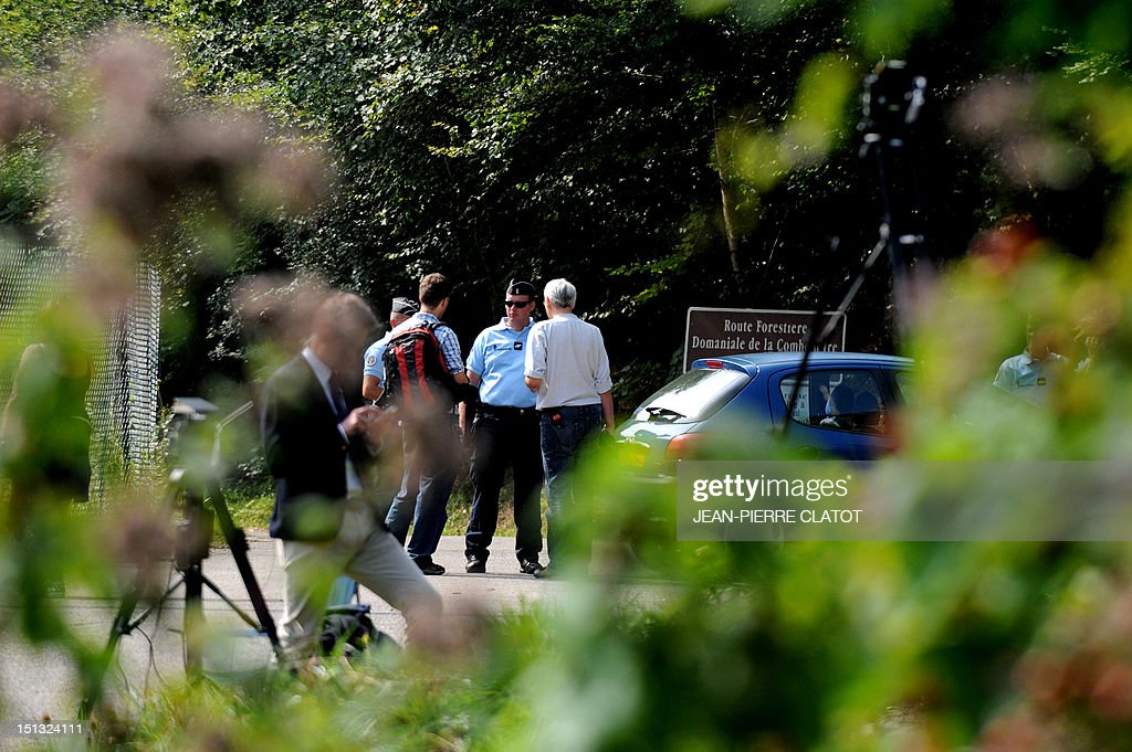 French gendarmes stand guard near journalists on the 'Combe d'Ire' road in the French Alpine village of Chevaline on September 6, 2012, where four people were shot dead. A four-year-old girl spent hours curled up under her mother's body and miraculously survived the deadly attack that left her father, mother and grandmother dead and her elder sister seriously injured, officials said.