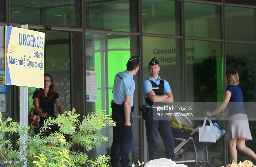 French gendarmes stand guard on September 10, 2012 at the entrance of the Grenoble's CHU Hospital French Alps, where the elder of two child survivors of the French Alps shooting remained under sedation. Zainab al-Hilli, 7, is recovering from a fractured skull and a bullet wound in the shoulder which she incurred in the September 5 attack in which her parents, grandmother and a passing French cyclist were killed. (L) a board showing the way to the emergency unit for gynecology and maternity ward.