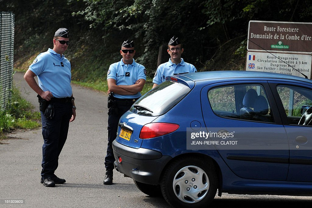 French gendarmes stand guard on the 'Combe d'Ire' road in the French Alpine village of Chevaline on September 6, 2012, where four people were shot dead. A four-year-old girl spent hours curled up under her mother's body and miraculously survived the deadly attack that left her father, mother and grandmother dead and her elder sister seriously injured, officials said.