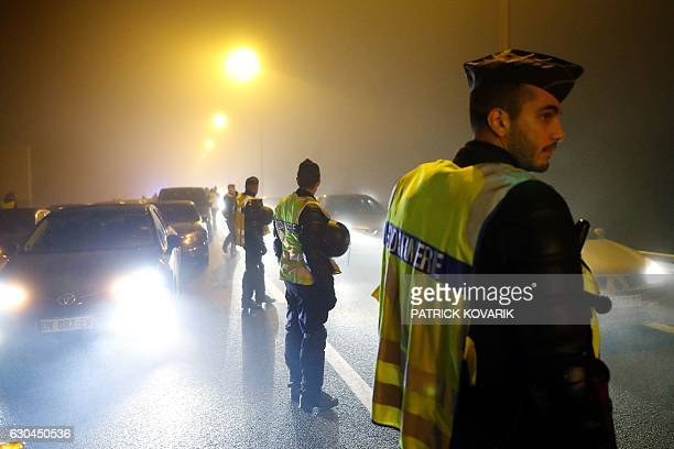 French gendarmes stand guard whilst VTC drivers try to block part of the highway leading to the Paris CharlesdeGaulle airport in Roissy on December...