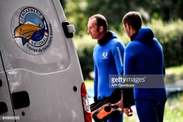 French gendarmes stand next to their vehicle on wich the logo of the gendarmerie's sonar detection unit is seen on September 11 2017 in...