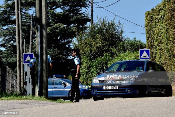 French gendarmes stand next to their vehicles in front of the house of a man charged with kidnapping following the disapperance of a nineyearold girl...