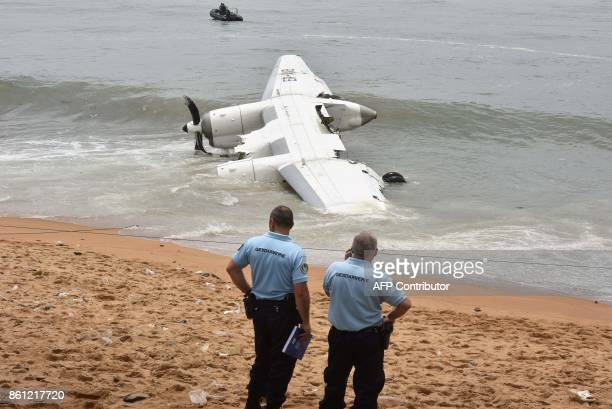 French Gendarmes stand on the beach of PortBouet in Abidjan near the wreckage of a cargo plane that crashed off Ivory Coast killing four on October...