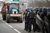 TOPSHOT French gendarmes stand on the RN 165 motorway facing protesters in a tractor bearing a sign reading 'Enough with Le Foll klore help we are...