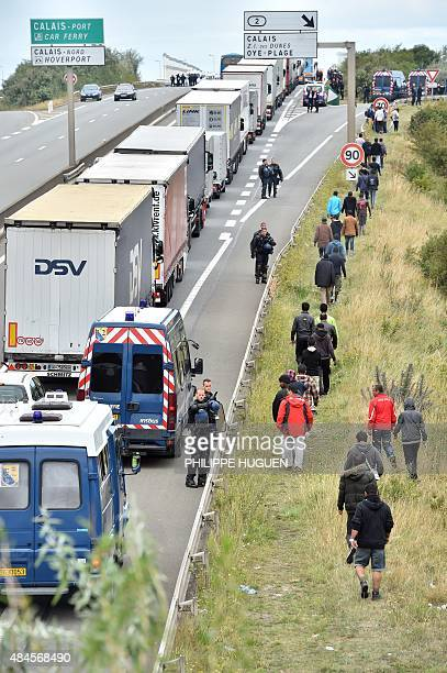 French gendarmes stand on the side of the road to prevent migrants from approaching lorries on the road leading to the ferry port in Calais northern...