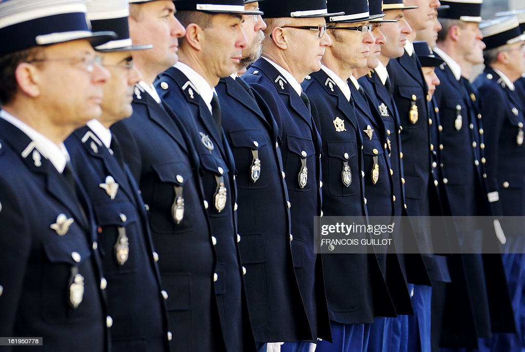 French gendarmes stand to attention during a memorial cemerony honoring gendarmes who died during service, on February 18, 2013 at the Hotel des Invalides in Paris.
