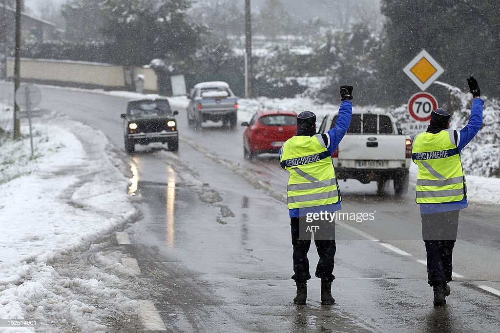 French gendarmes stop cars to control snow equipment on a snow covered road near Ajaccio on February 24, 2013, in Corsica.