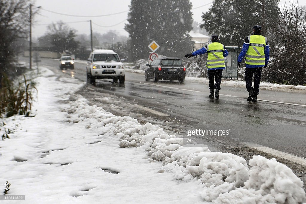 French gendarmes stop cars to control snow equipment on a snow covered road near Ajaccio on February 24, 2013, in Corsica. AFP PHOTO / PASCAL POCHARD-CASABIANCA