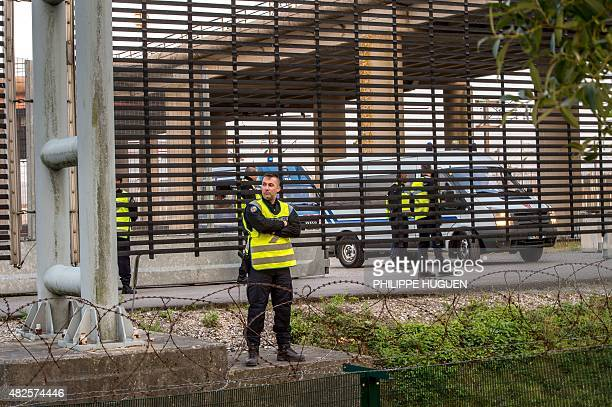 French gendarmes take up positions around the closed gate of the boarding platform of the Eurotunnel site to block migrants who try to cross it in...