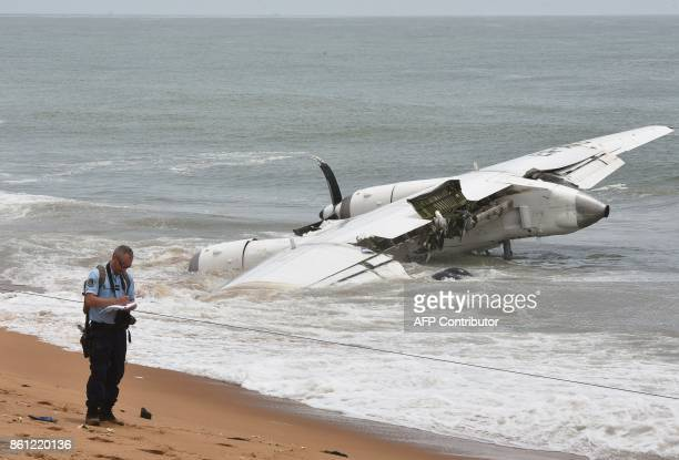 A French Gendarmes takes notes on the beach of PortBouet in Abidjan near the wreckage of a cargo plane that crashed off Ivory Coast killing four on...
