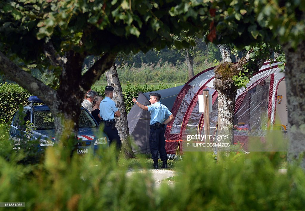 French gendarmes talk with investigators near the caravan of the British family hit by gun attack on September 6, 2012 in the camping 'Le Solitaire du lac' in the French Alpine village of Saint-Jorioz. A four-year-old girl spent hours curled up under her mother's body and miraculously survived the deadly attack that left her father, mother and grandmother dead and her elder sister seriously injured, officials said. AFP PHOTO/PHILIPPE DESMAZES