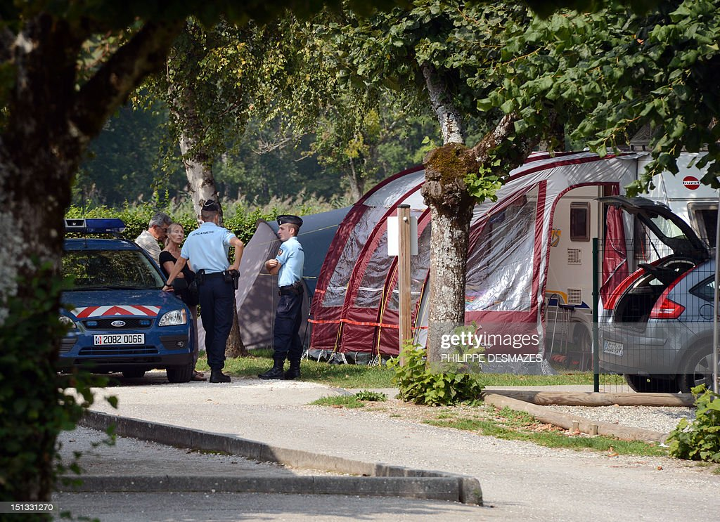 French gendarmes talk with investigators near the caravan of the British family hit by gun attack on September 6, 2012 in the camping 'Le Solitaire du lac' in the French Alpine village of Saint-Jorioz. A four-year-old girl spent hours curled up under her mother's body and miraculously survived the deadly attack that left her father, mother and grandmother dead and her elder sister seriously injured, officials said.