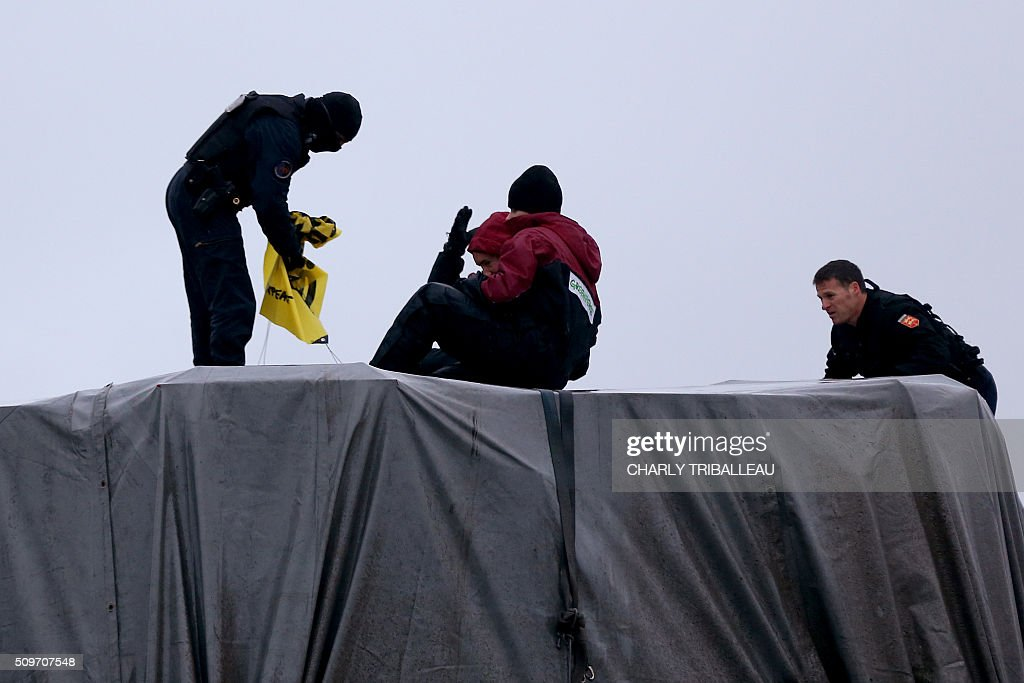 French gendarmes try to remove Greenpeace's activists from the top of a trailer of a special convoy transporting a lid that is to be installed on the vessel of the nuclear reactor EPR, currently under construction at Flamanville, in Evrecy, northernwestern France, on February 12, 2016. The convoy transporting the lid of 110 tons that measures 5,5 meters in diameter left the Areva plant on Chalon-sur-Saone, eastern France, on the morning of February 8 and is expected to arrive at its destination on February 12. / AFP / CHARLY TRIBALLEAU