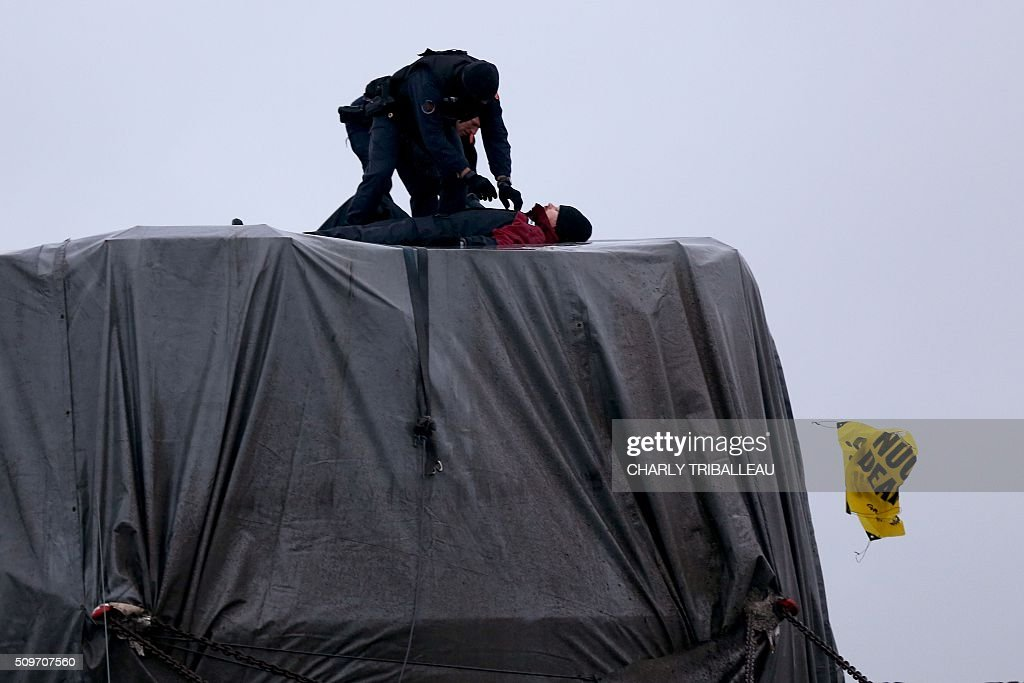 French gendarmes try to remove Greenpeace's activists from the top of a trailer of a special convoy transporting a lid that is to be installed on the vessel of the nuclear reactor EPR, currently under construction at Flamanville, in Evrecy, northernwestern France, on February 12, 2016. The convoy transporting the lid of 110 tons that measures 5,5 meters in diameter left the Areva plant on Chalon-sur-Saône, eastern France, on the morning of February 8 and is expected to arrive at its destination on February 12. / AFP / CHARLY TRIBALLEAU