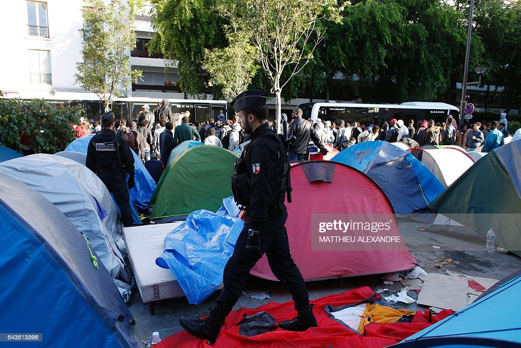 French Gendarmes walk among the tents of a camp as they proceed to the evacuation of migrants at the Pajol hall on June 29, 2016 in Paris. The police started early on June 29, 2016, the evacuation of several hundreds of migrants, from a camp at the former SNCF Hall 'Pajol'. / AFP / MATTHIEU