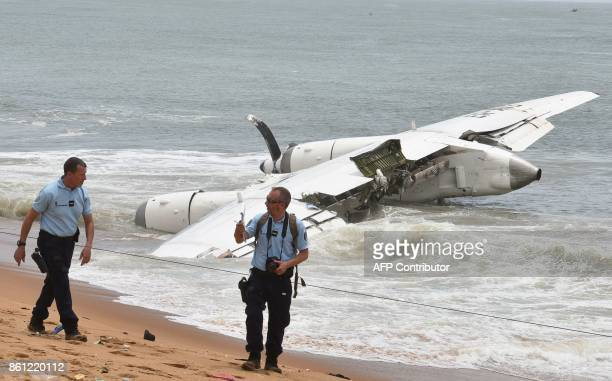 French Gendarmes walk on the beach of PortBouet in Abidjan near the wreckage of a cargo plane that crashed off Ivory Coast killing four on October 14...