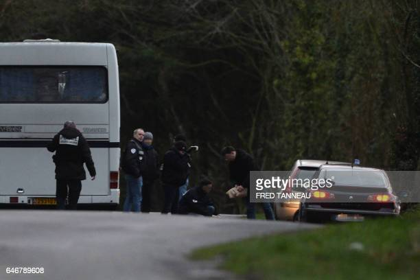 French gendarmes work on a road near the site where a jogger found a healthcare card in the name of a missing person on March 1 in Dirinon some 20 km...