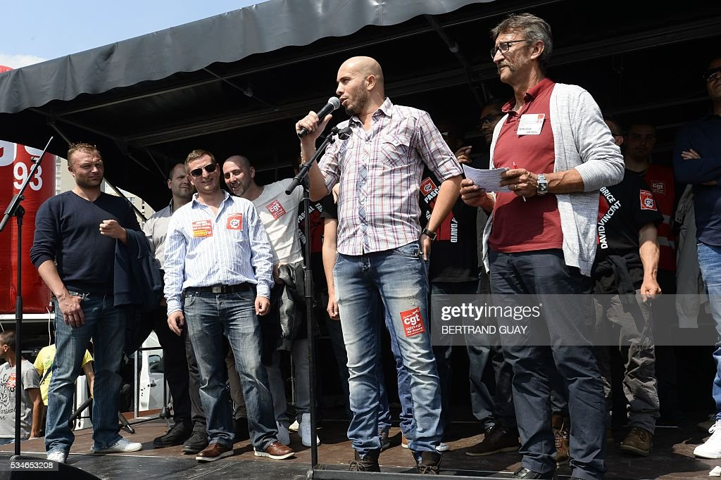 French General Confederation of Labour (CGT) union's member stand on a stage outside the court of Bobigny, northern Paris on May 27, 2016 as the trial of 15 French CGT union's members judged for the episode of the torn shirt was referred to September, in full showdown initiated by the union with the government on labor law. On October 5, 2015 under the cries of naked, naked and resignation , the Air France human resources director found himself shirtless, tattered shirt during a protest after the announcement of a restructuring of the airline threatening nearly 3,000 jobs.