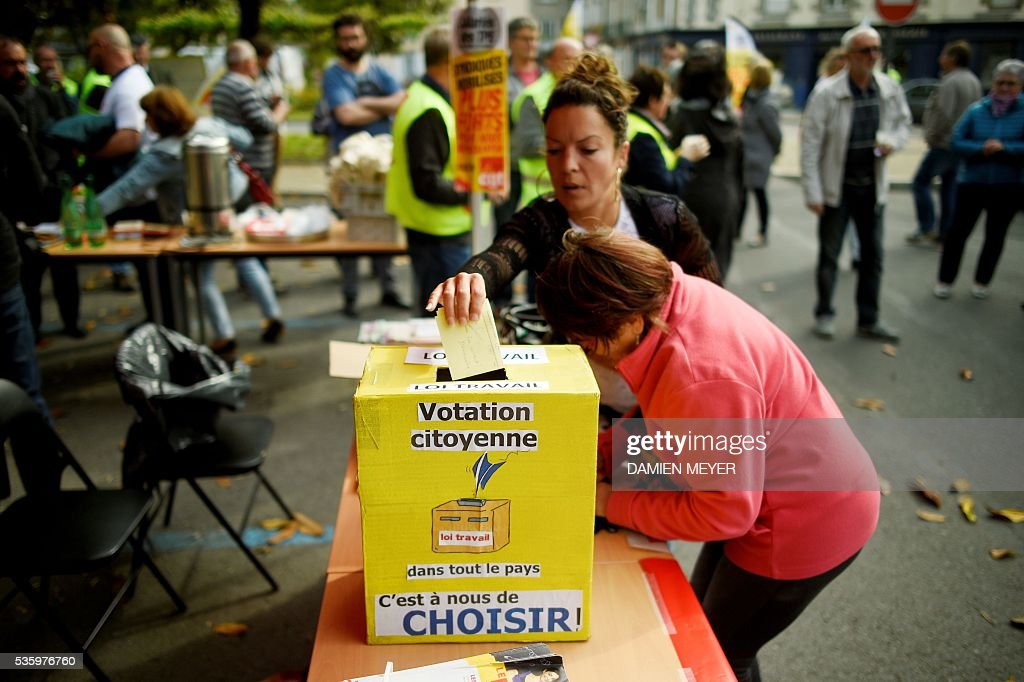 A French General Confederation of Labour (CGT) union's militant casts her ballot against the new labour law in Fougeres, western France on May 31, 2016, during a visit of CGT union's secretary-general. French secretary-general of the General Confederation of Labour (CGT) worker's union Philippe Martinez declared that the CGT filed a lawsuit for defamation against the head of France's bosses' federation. French employers' association Medef Pierre Gattaz accused unions of behaving like 'terrorists', as the fresh industrial unrest was set to hit transport just days before fans begin arriving for the start of the football championships on June 10. / AFP / DAMIEN