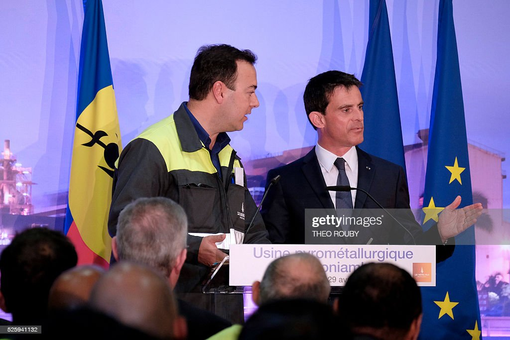 French general director of SLN Jerome Fabre stands by French Prime Minister Manuel Valls as he delivers a speech after visiting the metallurgic factory SLN on April 29, 2016, in Noumea. Valls said France would be willing to loan 200 millions euros to save the SLN factory, the main producer of nickel in New Caledonia. / AFP / THEO