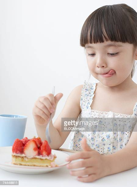 French girl holding fork in front of strawberry