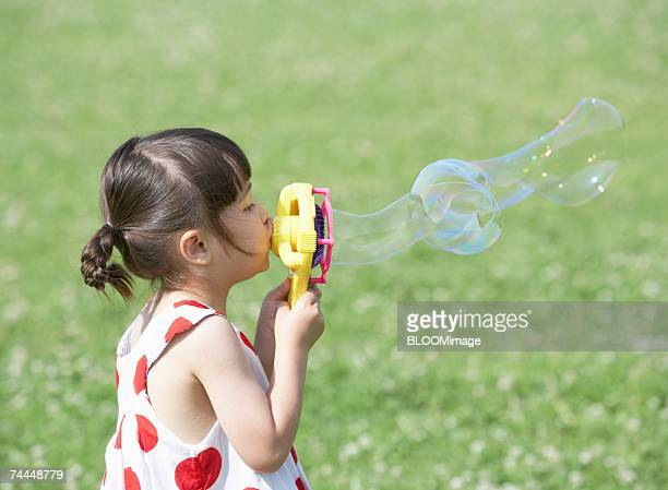 French girl wearing dress playing with bubbles on meadow ,outside