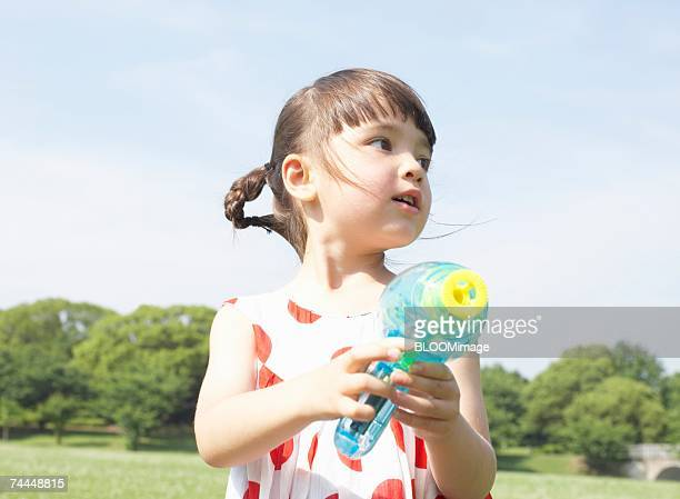 French girl wearing dress playing with water gun ,outside