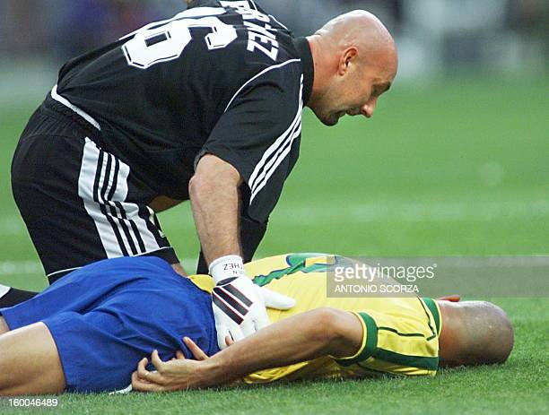 French goalkeeper Fabien Barthez kneels on the pitch next to Brazilian striker Ronaldo after jumping over him 12 July at the Stade de France in...