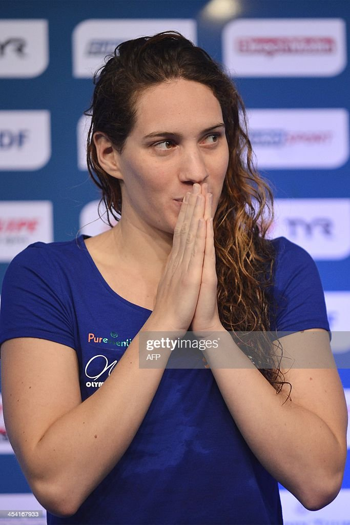 French gold winner <a gi-track='captionPersonalityLinkClicked' href=/galleries/search?phrase=Camille+Muffat&family=editorial&specificpeople=596271 ng-click='$event.stopPropagation()'>Camille Muffat</a> reacts on the podium after her victory in the women's 100m Butterfly event at French short course swimming championships in Dijon, central-eastern France, on December 7, 2013. AFP PHOTO / ROMAIN LAFABREGUE