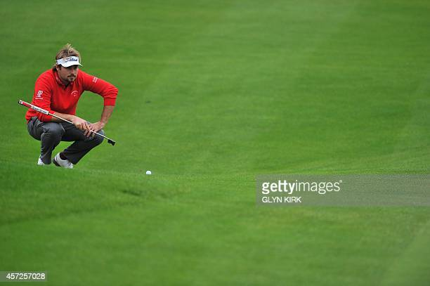 French golfer Victor Dubuisson lines up his putt to the 15th green in his match against Spanish golfer Pablo Larrazabal during the first day of the...